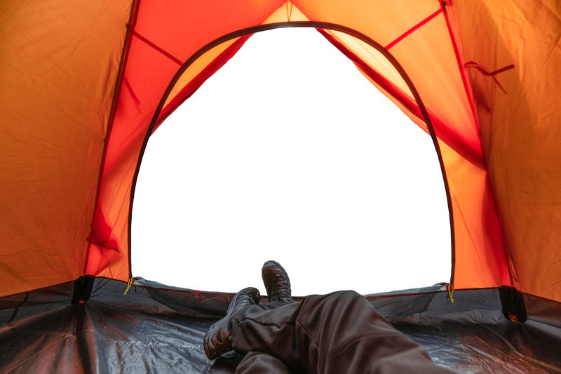 Rear view of man relaxing on tent