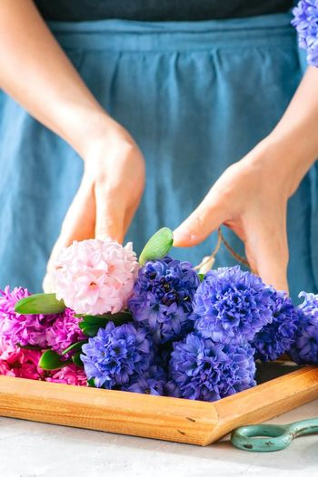 Midsection of woman holding flowers in tray on table
