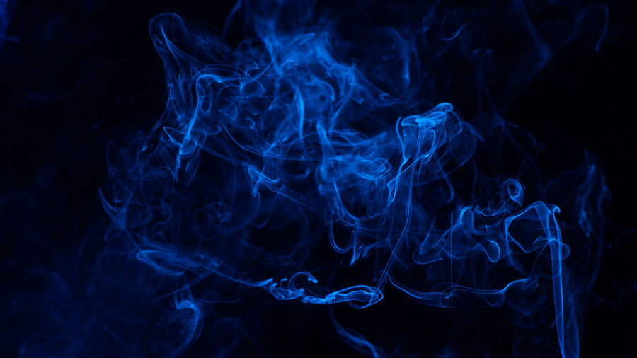 Conceptual image of blue color smoke isolated on dark black background, halloween concept design.