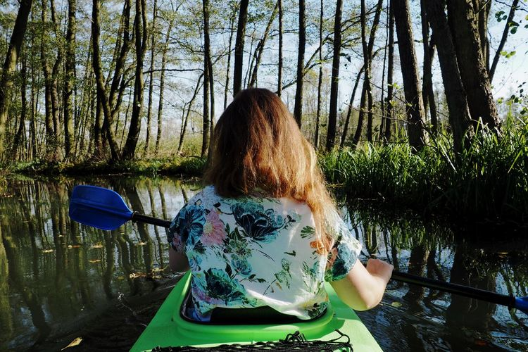 Rear View Of Woman Canoeing On Lake At Forest
