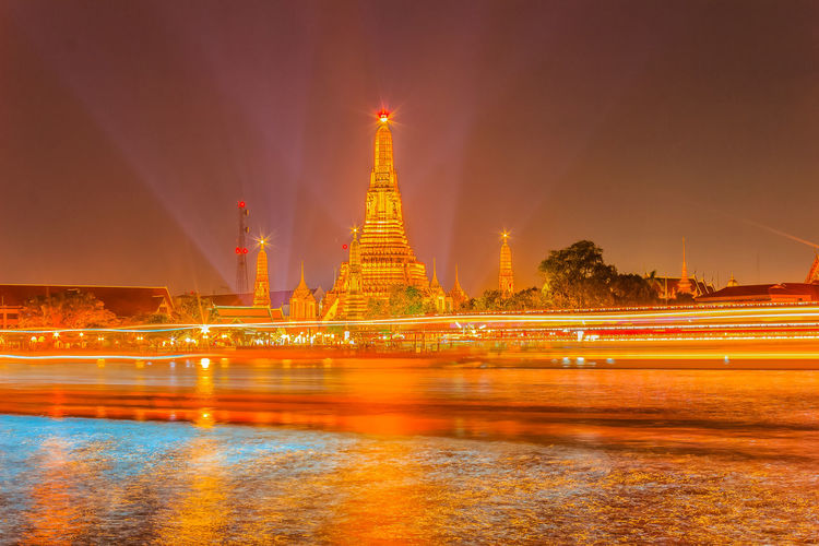 Beautiful cityscape view of Wat Arun Rajwararam temple with light trail from the Chao Phraya river cruises and light shows at night, the popular tourist attraction and one of the symbols of the city. Wat Arun Wat Arun (Temple Of Dawn) Wat Arun Ratchawararam Ratchawarama Wat Arun Temple Wat Arun Temple, Thailand Wat Arun, Bangkok Architecture Building Exterior City Gold Colored Illuminated Long Exposure Motion Nature Night No People Outdoors Reflection Religion River Sky Spirituality Travel Destinations Water Waterfront