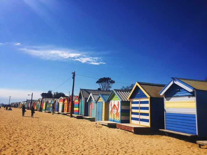 Colorful beach huts against blue sky