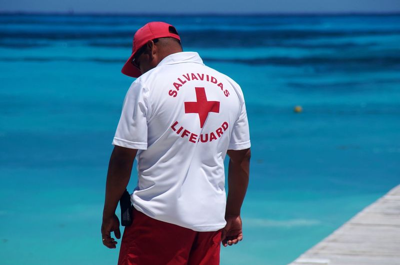 Rear view of lifeguard standing by sea