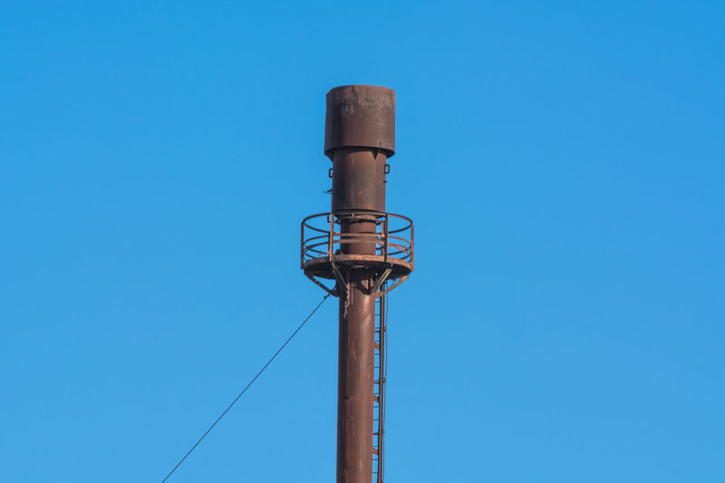 Chimney for controlled burning off of excess gas. Chimney Flame Blue Burn Controlled Cable Clear Sky Close-up Combustion Connection Copy Space Day Exhaust Gases Flaring Are Atmosphere Low Angle View No People Outdoors Technology Vent