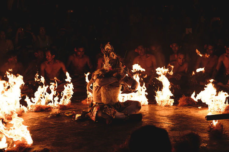 Man surrounded by fire and people during traditional festival at night