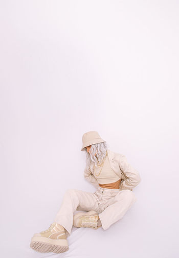 Midsection of woman sitting against white background