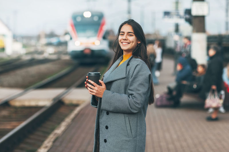 Portrait of smiling young woman using phone while standing on road