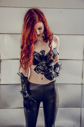 Beautiful redhead in costume standing against wall