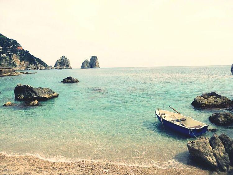 Marinapiccola with view on Faraglioni with a small boat in the Sea of Capri
