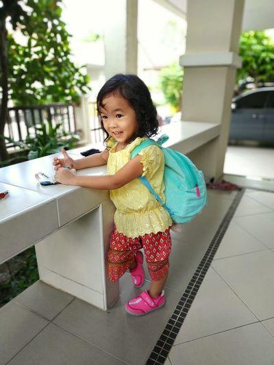 Full length of smiling girl with backpack standing on floor