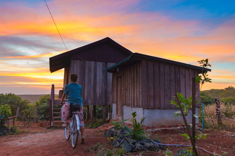 Sunset Sky Transportation Built Structure Architecture Real People One Person Lifestyles Cloud - Sky Men Orange Color Nature Rear View Building Exterior Casual Clothing Leisure Activity Land Vehicle Mode Of Transportation Bicycle Outdoors