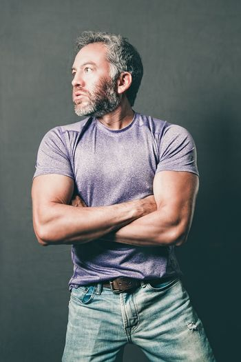 Confident Man With Arms Crossed Looking Away Against Wall