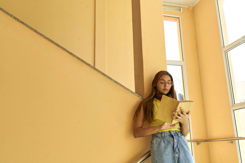 Portrait of smiling young woman standing against yellow wall