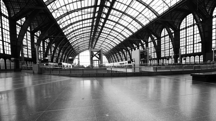 Antwerpen Antwerp Train Station Train Station EyeEm Best Shots - Black + White Blackandwhite Touristic Attraction Metal Construction Monochrome Famous Building Historical Building Indoors  Historical Buildings Indoors  Architecture Ceiling Built Structure Transportation Arch Flooring Glass - Material Incidental People Travel Mode Of Transportation Building Reflection Empty Glass Tiled Floor Railroad Station Window