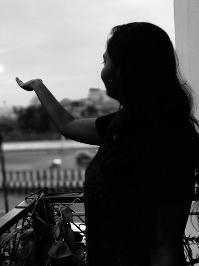 Side View Of Woman Gesturing While Standing In Balcony