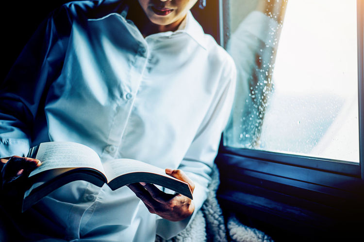 Midsection of woman reading book by window