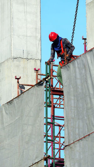 Low angle view of man working at construction site