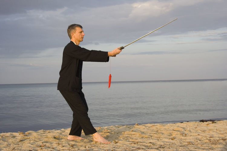 Man practicing tai chi at beach against cloudy sky