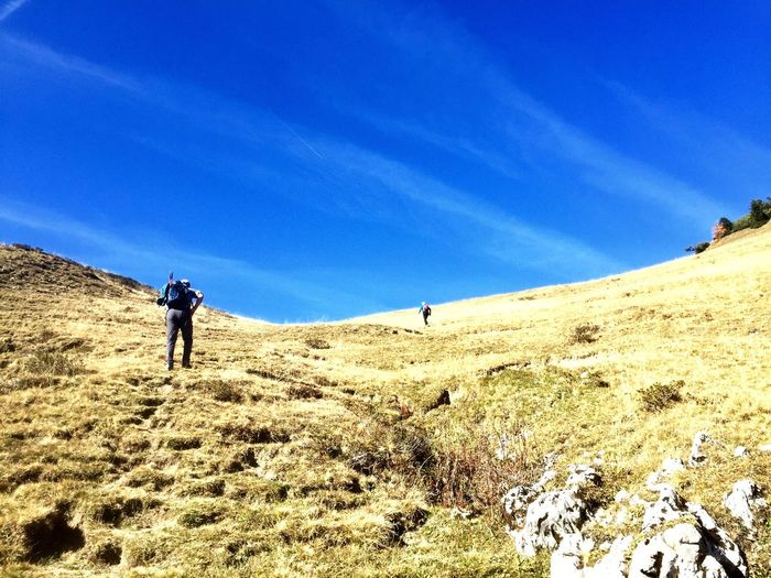 Low angle view of people climbing on mountain against blue sky during sunny day