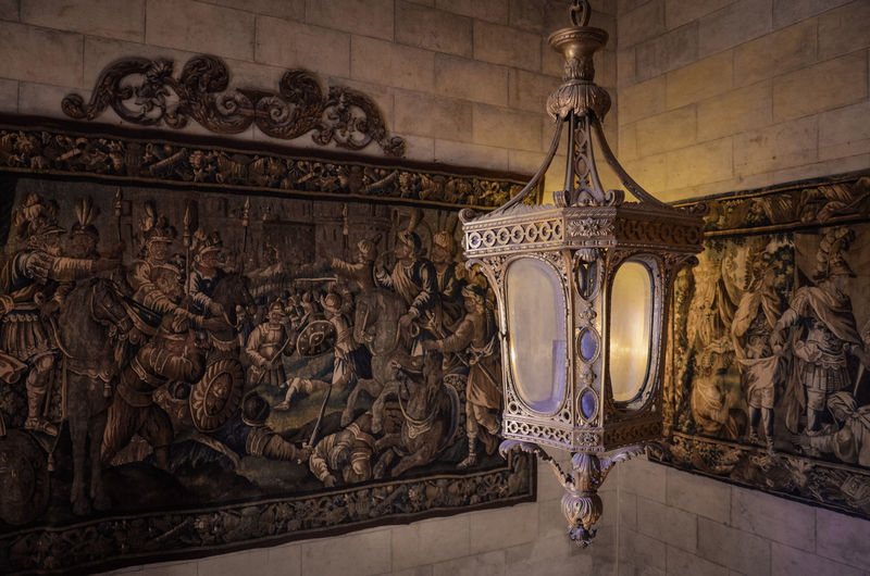 Old lamp hanging by paintings on wall of castle