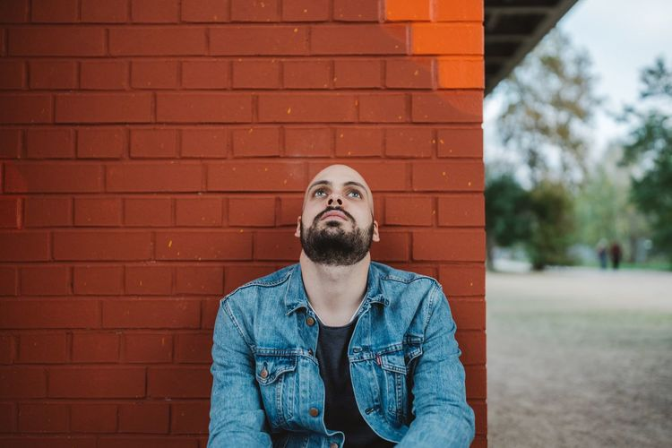 Look up to the sky Brick Wall Beard Casual Clothing One Person Front View Leisure Activity Lifestyles Men Outdoors Real People Young Adult Day Denim Jacket Adult One Man Only People Adults Only Full Frame Lookingup Man Model Young Men Sitting Asian Squat European