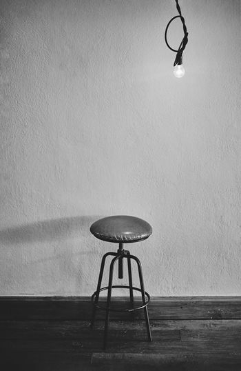 Low angle view of lamp on table against wall