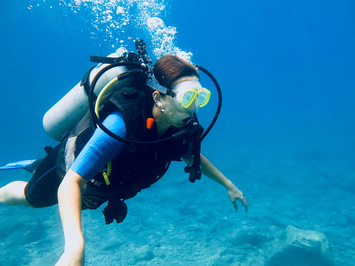 Brunette girl scuba diving in the warm ocean waters of southern turkey