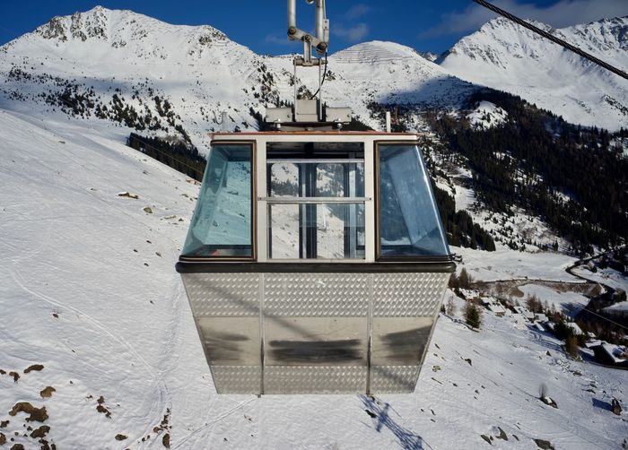 Cabin of cable car against snow covered mountain