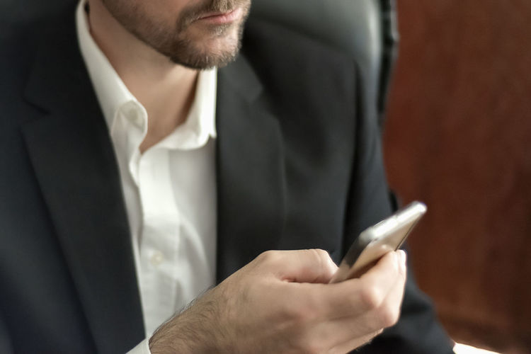 Midsection of businessman using smart phone in office