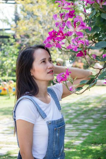 Portrait of beautiful woman standing by flowering plants