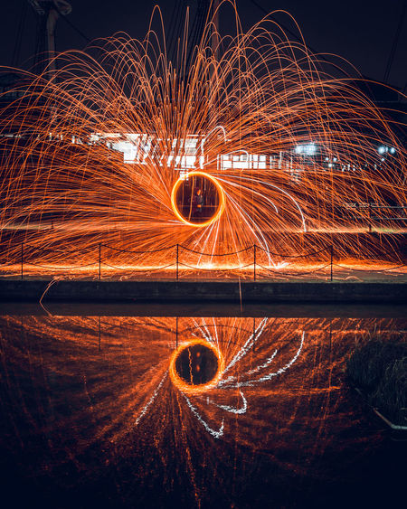 Person Spinning Wire Wool Reflecting In Calm Water