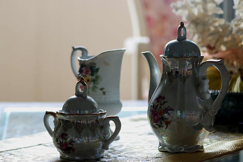 Close-up of teapot by container on table