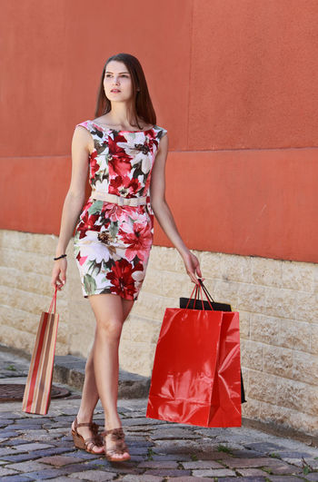 Full length of woman holding shopping bags walking on street