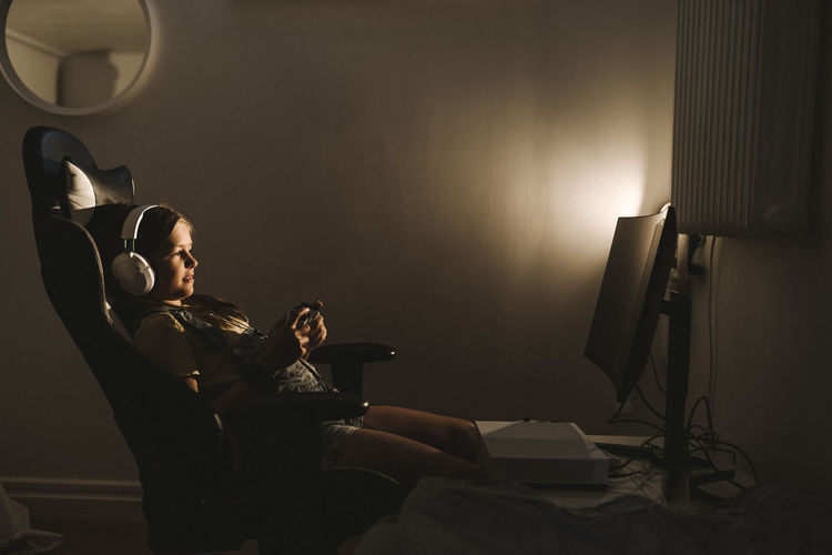 Woman sitting by illuminated lamp at home
