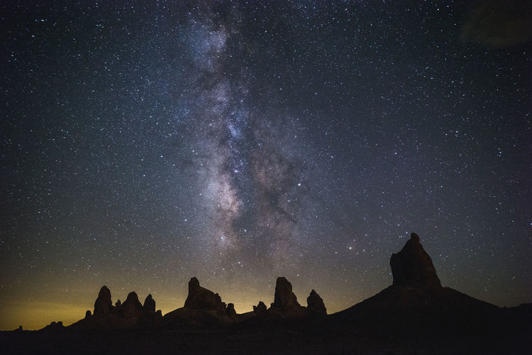 Low angle view of silhouette mountain against star field