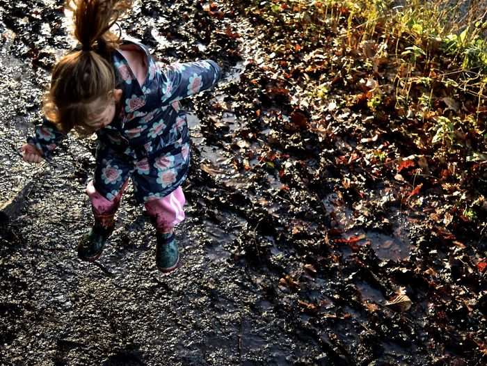 High Angle View Of Girl Jumping In Mud On Field