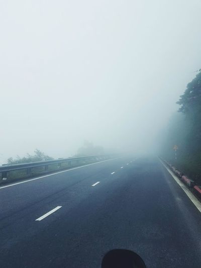 Road by fog against sky