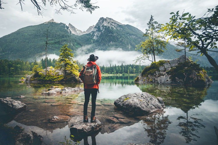 Rear view of woman looking at lake against mountains