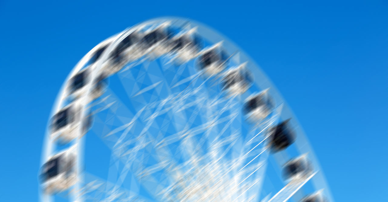 CLOSE-UP OF ROLLERCOASTER AGAINST CLEAR BLUE SKY