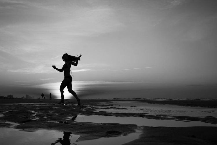 Rise and Shine Sky Silhouette Water Land Sea Lifestyles Beach Leisure Activity One Person Full Length Nature Beauty In Nature Real People Scenics - Nature Tranquil Scene Tranquility Trip Vacations Human Arm Outdoors Arms Raised Blackandwhite Black And White Girl Young Women Teenager Fun Joy Sunrise Shadow Ocean Sand Surf