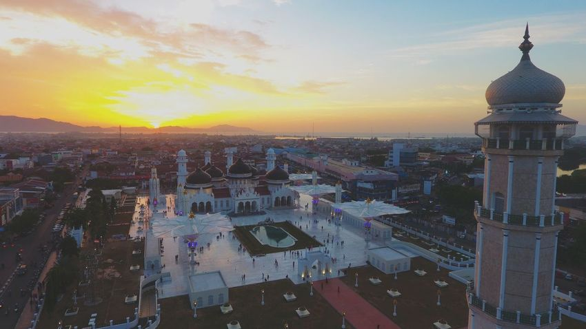 Baiturrahman Mosque Baiturrahman Mosque Building Exterior Architecture Built Structure City Sunset Sky Cityscape Building Residential District Cloud - Sky Tower Travel Destinations Skyscraper Crowd Orange Color Office Building Exterior Nature High Angle View Outdoors Crowded