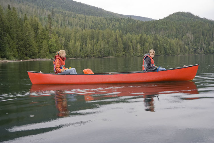 Siblings canoeing on clearwater lake at wells gray provincial park