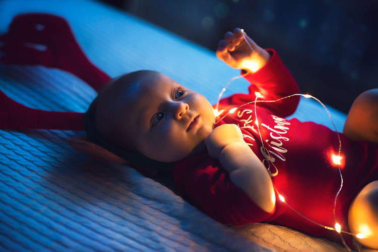 Cute baby by illuminated lights at home