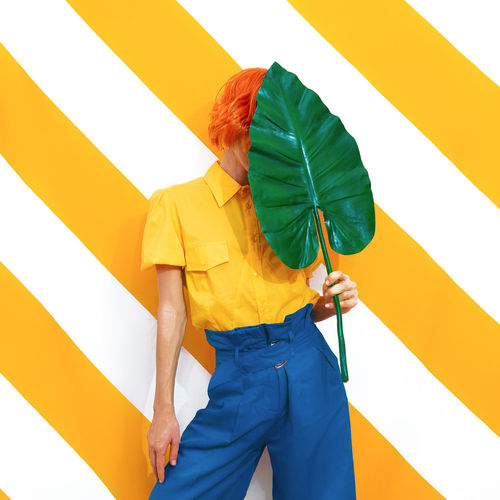 Unrecognizable model holding palm leaf and wearing vintage look on trendy striped yellow background