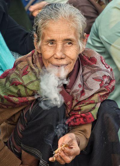 High angle view of woman smoking bidi while looking away