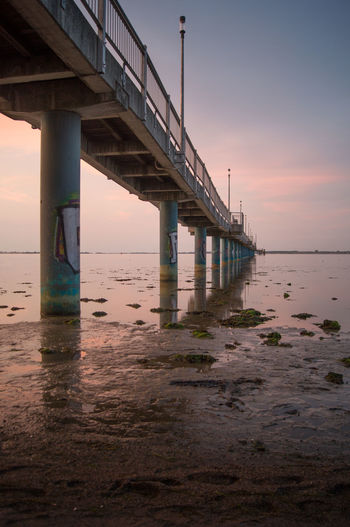 Low angle view of bridge over sea against sky during sunset