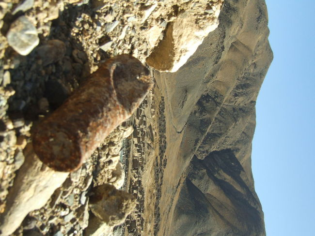 A shell casing lies rusted...a reminder of the grim battles fought against occupation forces in Afghanistan ..an abandoned village can be seen in the background Afghanistan In Pictures Barren Hills Old Battlefields Remains Of A Village Rusted Shell Casing Struggle Against Occupation