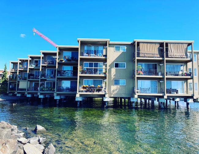 Buildings by lake against blue sky