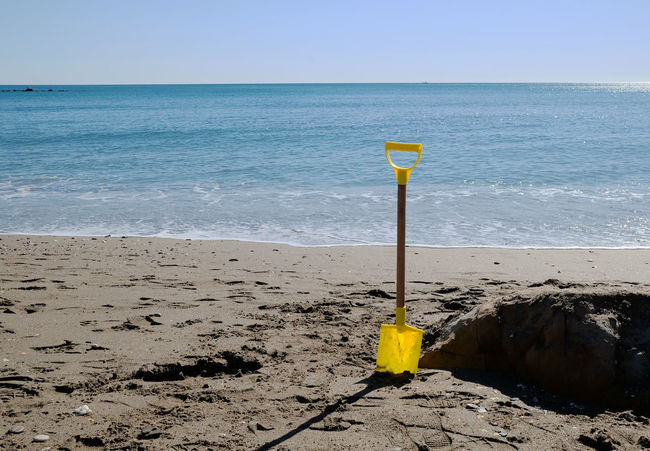 Abandoned Abandonment Beach Beauty In Nature Blue Child`s Play Clear Sky Day Digging Hole Holiday Horizon Over Water No People Outdoors Pit Sand Sea Shovel Live For The Story Toy Travel Water Yellow Yellow Shovel Paint The Town Yellow