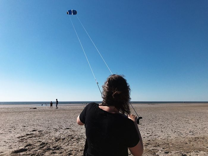Rear view of woman flying kite on beach against clear blue sky